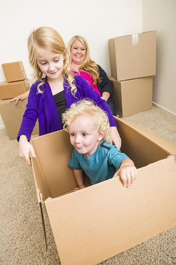 Boy and girl playing in a cardboard box while mother watches