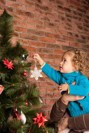 Young girl hanging a star on a Christmas tree
