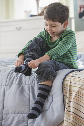 Young boy putting socks on