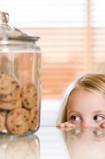 Young girl looking at a cookie jar