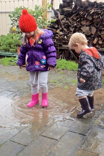 Young boy and girl playing in puddles