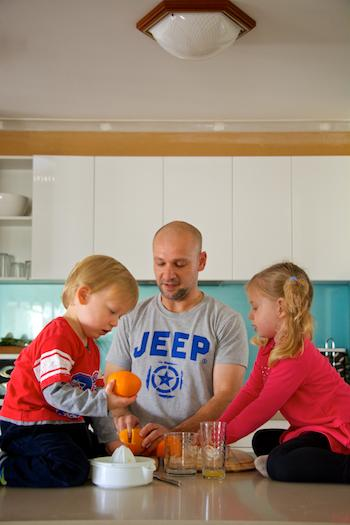 Father squeezing orange for juice with children