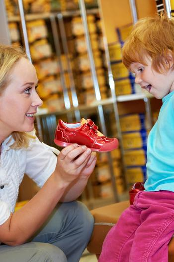 Woman showing new shoe to young boy