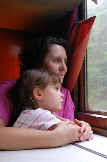 Mother and daughter looking out a train window